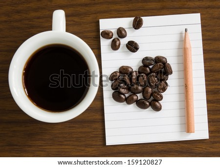 Coffee cup note paper and pencil decorated with coffee beans.