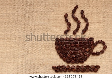 Coffee cup of coffee beans on burlap texture - stock photo