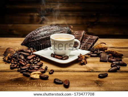 Coffee cup on a wooden table among coffee beans  and dark chocolate
