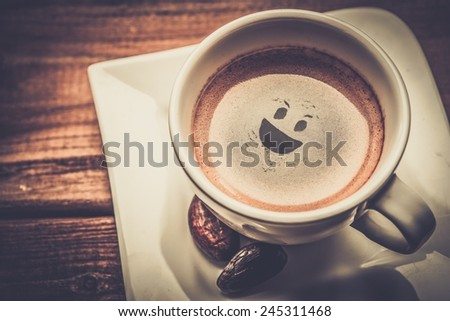 Coffee cup on a wooden table with smiley in it - stock photo