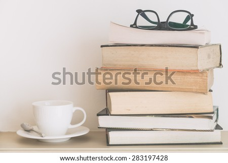 Coffee cup on book and eyeglasses with copy space for text - soft vintage filter - stock photo