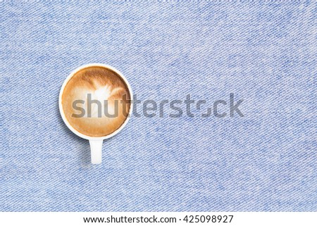 Coffee cup on jean tablecloth background top view flat lay copyspace