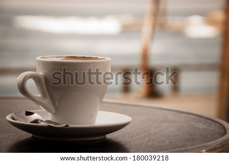 Coffee cup on round table in cafe terrace on the old pier with rusty railing and the view on the sea with waves in cold cloudy day. Loneliness idea. Aged photo. - stock photo