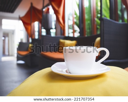 coffee cup on sofa pillow with blurred home interior background