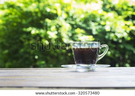 Coffee cup on table and green bokeh background - stock photo