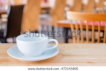 Coffee cup on table in cafe or restaurant with copy space.