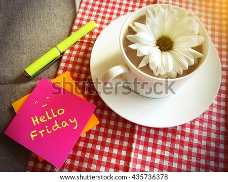coffee cup on table with white daisy and words Hello Friday vintage style - stock photo