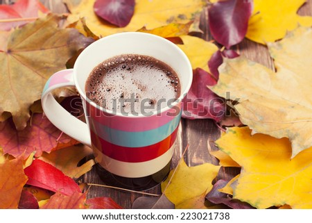coffee cup on the autumn fall leaves on wooden background