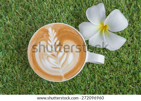 Coffee cup on the grass texture - stock photo
