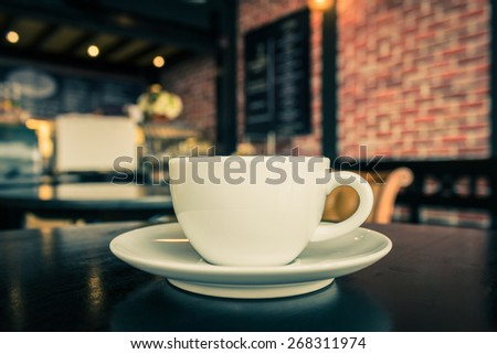 Coffee cup on the table at the coffee shop, vintage color tone. - stock photo