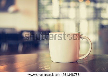 Coffee cup on the table in coffee shop - vintage tone with soft focus - stock photo