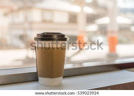 Coffee Cup on the Train table nest to Window with Morning Light