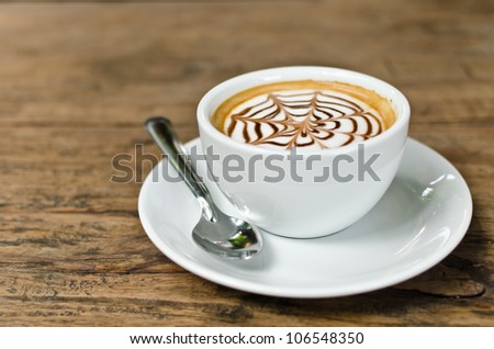 Coffee cup on the wood texture background, selective focus on coffee cream. - stock photo