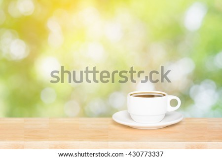 Coffee cup on the wooden table and green bokeh background