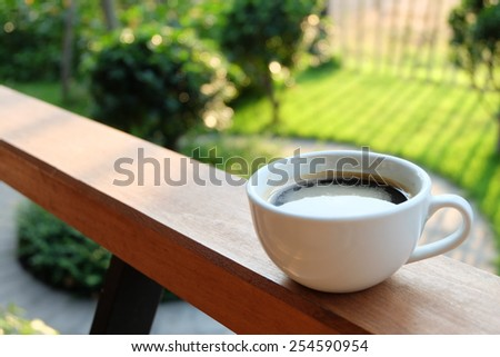 Coffee cup on wooden background in the garden  - stock photo
