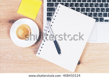 Coffee cup on wooden desktop with yellow sticker, keyboard and blank notepad. Topview - stock photo