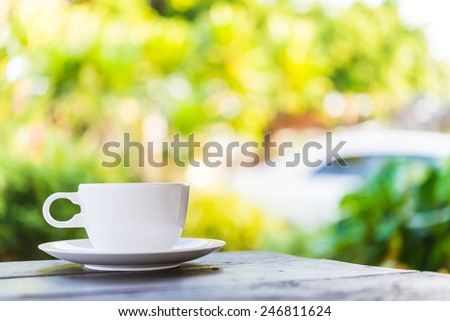 Coffee cup on wooden table outdoor background - stock photo