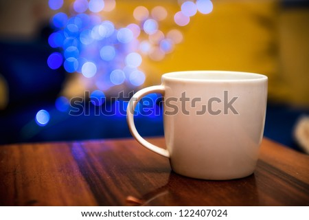 coffee cup on wooden table over blurred blue bokeh background - stock photo