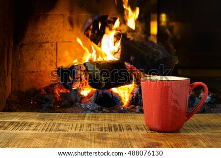 Coffee cup on wooden table over fireplace.