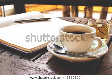 coffee cup on wooden table - vintage effect style pictures, over light [blur and select focus background]