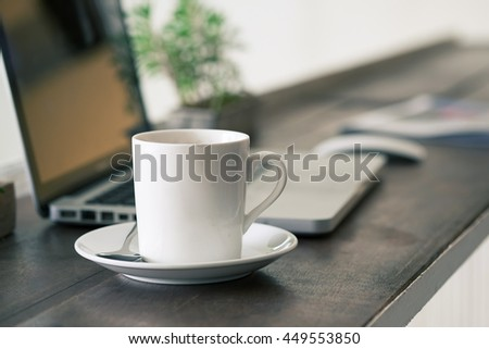Coffee cup on wooden work table.