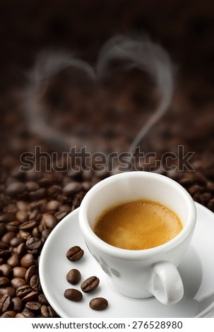 coffee cup over a heap of coffee beans - stock photo