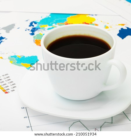 Coffee cup over world map and financial documents - 1 to 1 ratio - stock photo