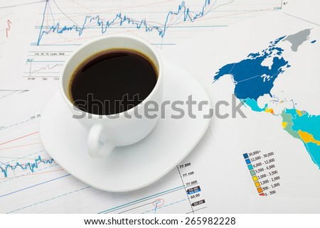 Coffee cup over world map and market charts