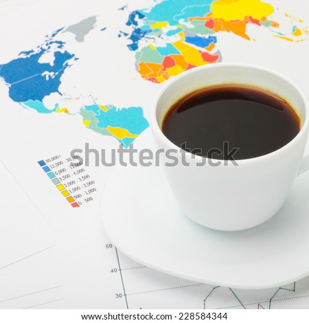 Coffee cup over world map and some financial documents - stock photo