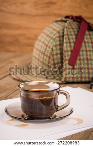 Coffee cup, paper sheets and detective hat on old Wooden table.