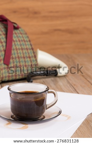 Coffee cup, paper sheets and detective hat on old Wooden table. - stock photo