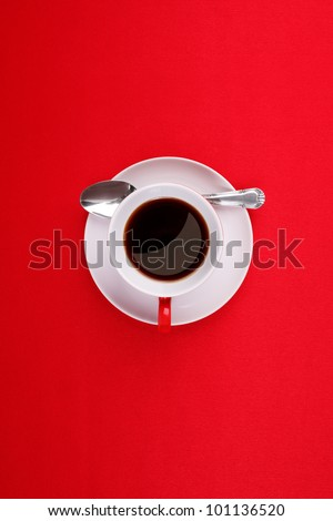 Coffee cup, saucer and spoon on a red background - stock photo