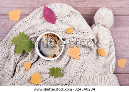 Coffee cup, scarf and hat handmade, dry leaves on a wooden background. Top view. Concept cozy atmosphere with a cup of coffee - stock photo