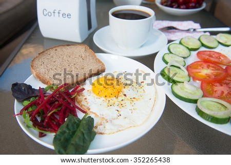 Coffee cup, scrambled eggs and salad breakfast on table - stock photo