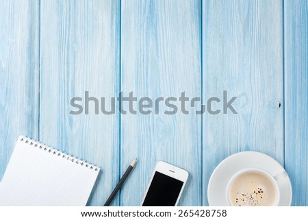 Coffee cup, smartphone and blank photo frame on wooden table background. Top view with copy space - stock photo