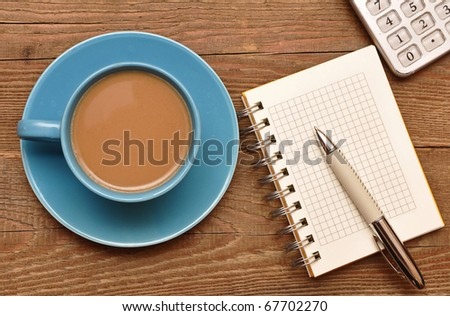 Coffee cup, spiral notebook and pen on the old wooden table - stock photo