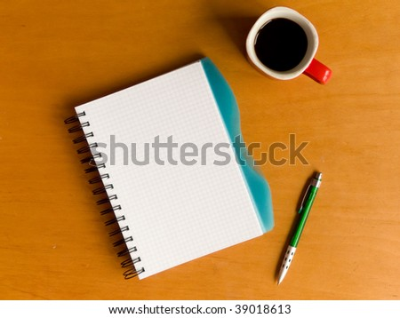 Coffee cup, spiral notebook and pen on the wooden table. Viewed from above.