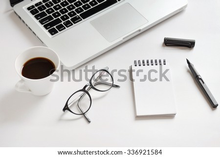 Coffee cup, spiral notebook, computer keyboard, glasses, and pen on white background - taken in natural light  with strong shodow to create realistic indoor mood