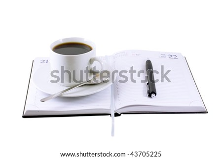 Coffee cup,  standing on the opened daily organizer . Isolated - stock photo