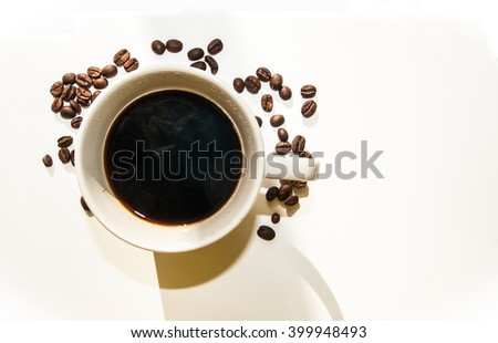 Coffee cup surrounded by coffee beans on white background