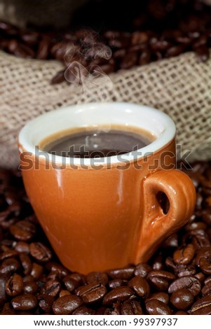 Coffee cup surrounded by toasted beans