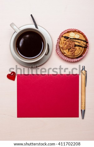 Coffee cup sweet cake cupcake and red paper blank with pen on wooden surface, top view copy space for text - stock photo