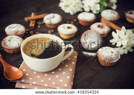 coffee cup, tasty seedcake and flower blossom on brown table - stock photo