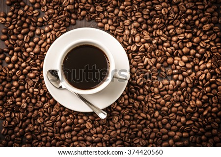 Coffee cup top view on beans background with spoon - stock photo