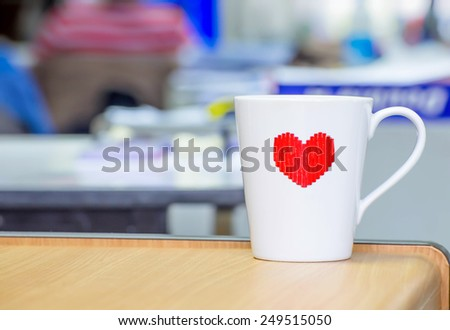 Coffee cup white heart-shaped placed on desk in the office. - stock photo