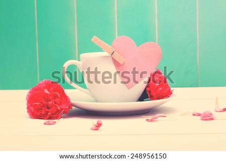 Coffee cup with a pink heart tag and carnations on a teal colored wood background - stock photo