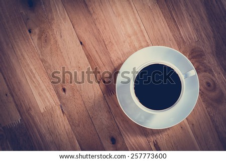 Coffee cup with black coffee on wooden table (top view) - soft focus with vintage color effect - stock photo