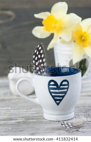 Coffee cup with blue heart, feathers and spring flowers in vase on wooden table. Spring, easter or gardening concept - stock photo
