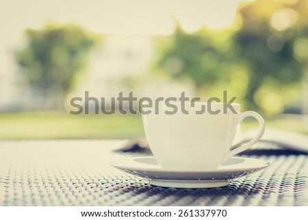 Coffee cup with book on blurred green nature background - vintage tone - stock photo