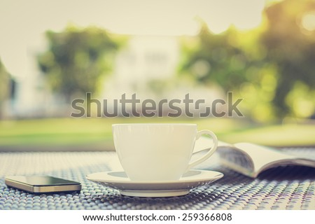 Coffee cup with book  & smartphone on the table in blurred green nature background - vintage style colors, soft focus - stock photo